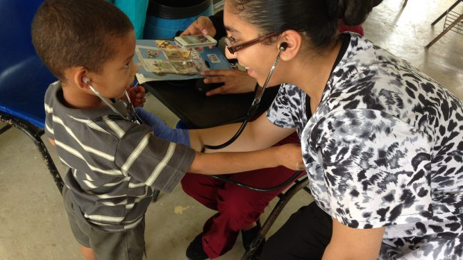 Macaulay student Kawsar Ibrahim '15 with patient at her internship/research