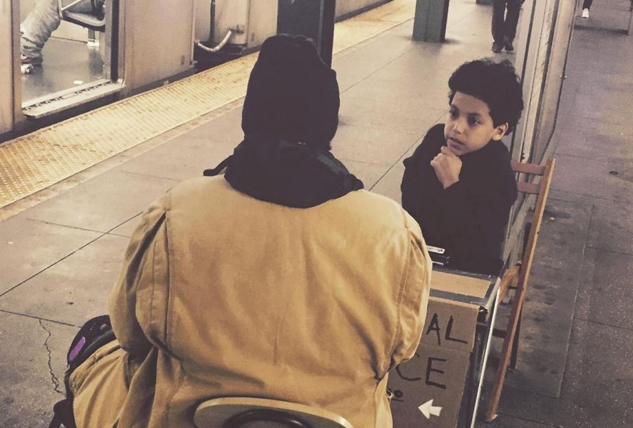 Photo of 11-year old giving advice in subway station to a passenger