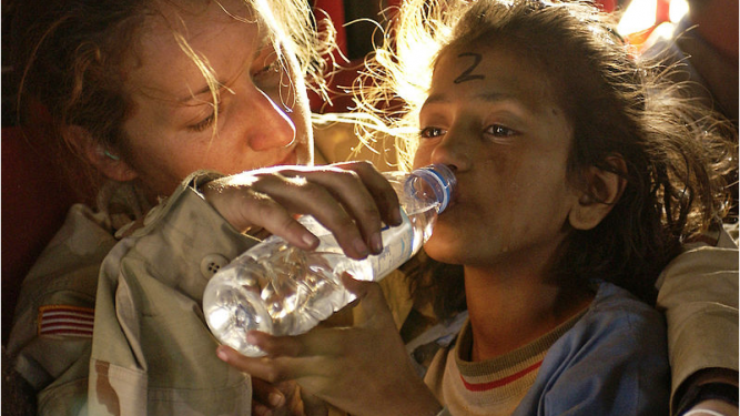 U.S. Army Sergeant Kornelia Rachwal gives a young Pakistani girl a drink of water as they are airlifted from Muzaffarabad to Islamabad, Pakistan, aboard a U.S. Army CH-47 Chinook helicopter on the 19 October 2005.