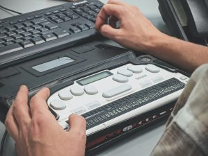Picture of a person using a braille screen reader.